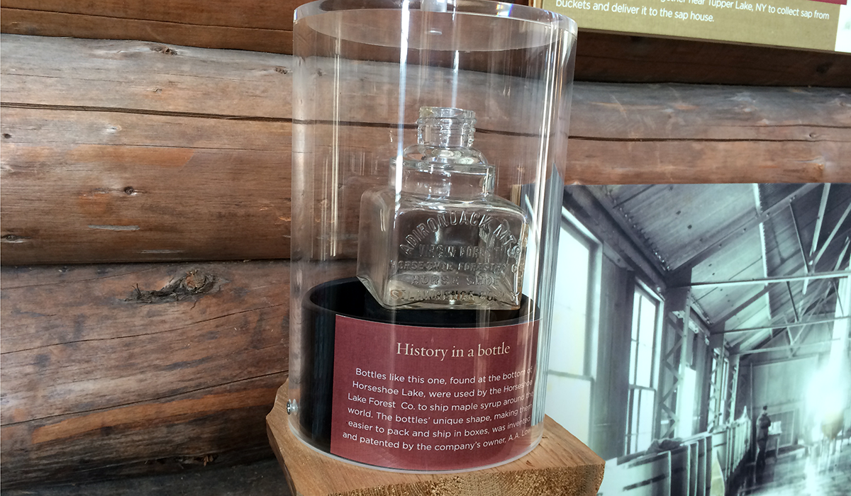 "One of A.A. Low's square bottles used to ship maple syrup is now on display at The Wild Center. The bottle was fished out of Horseshoe Lake by one of ""Tupper's Tappers."""