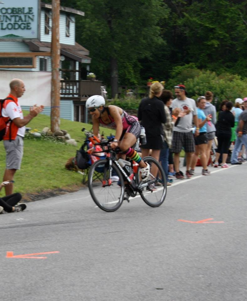 Amy Farrell rounds a bend in the bike portion of the Lake Placid Ironman with a smile on her face