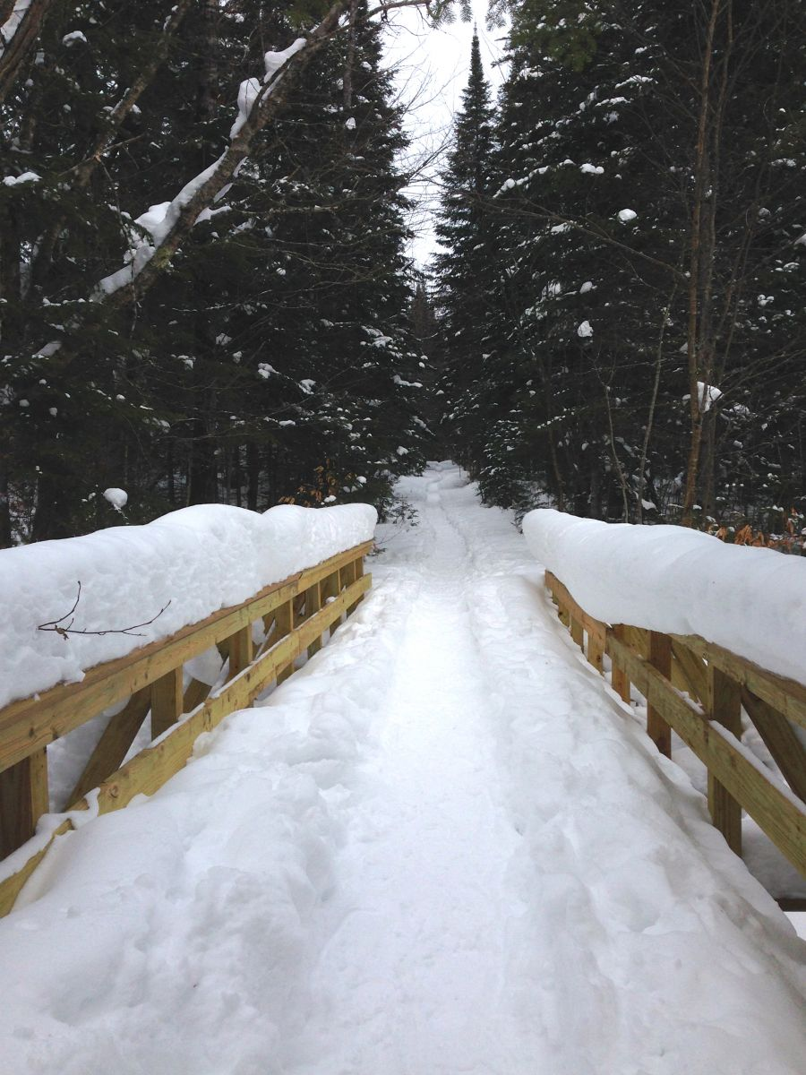 A snow-covered bridge at the start of the trailhead shows how well packed the trail is thanks to many climbers making their way up the mountain.