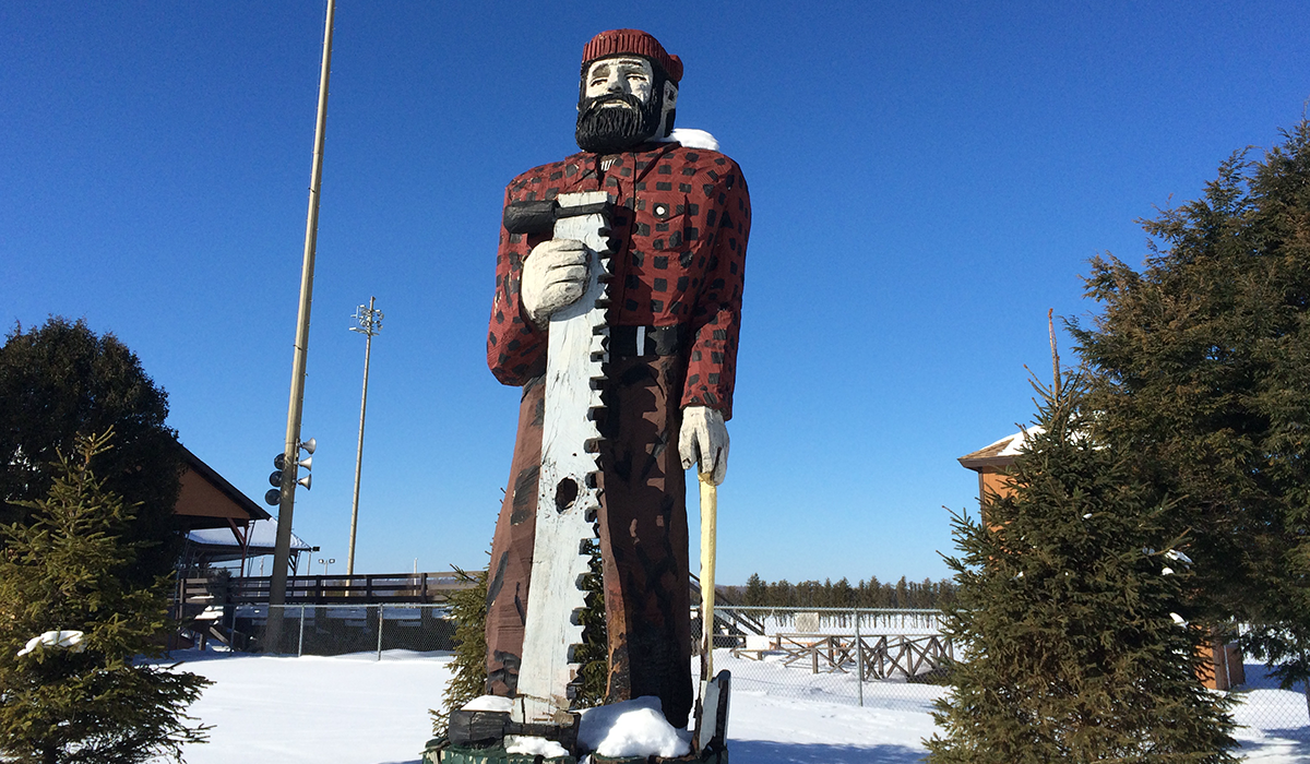 """The lumberjack statue at the Tupper Lake Municipal Park. He looks kind of lonely standing there in the snow... Maybe he should use the WiFi in the park to search for his soul mate on lumbermatch.com the online dating site where, and I quote: """"beardies meet beauties."""" (Yes, this is a real website.)"""