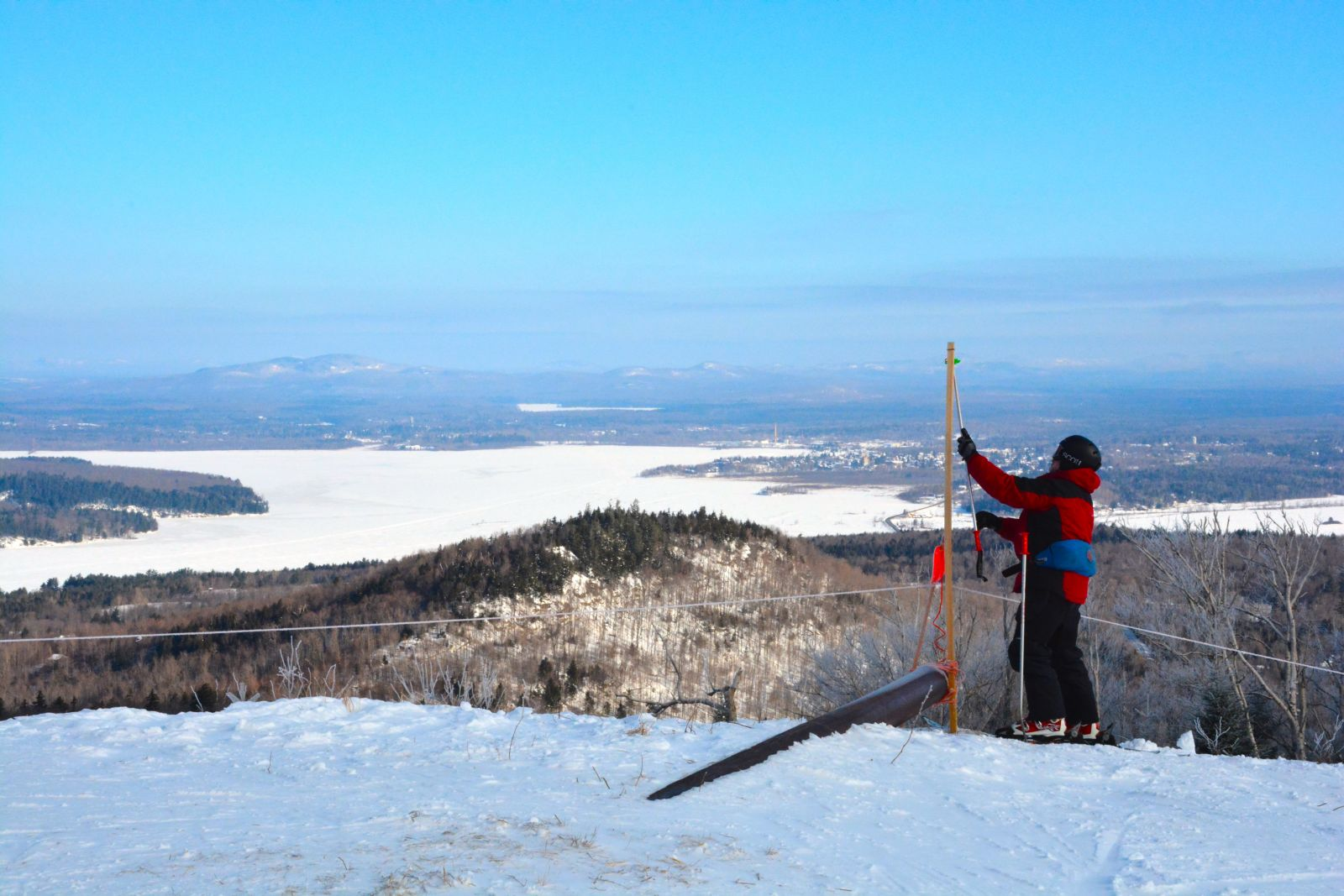 Mike Moore, a Big Tupper patroller, sets up a spot to hang the American Flag at the top of Chair 2