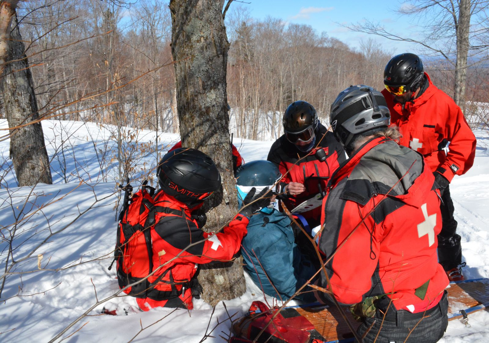 A team of Mitch Harriman, Anne Maltais, Adam Hurteau, and Dan King work together on training scenario two in the woods off of the Lift Line trail.