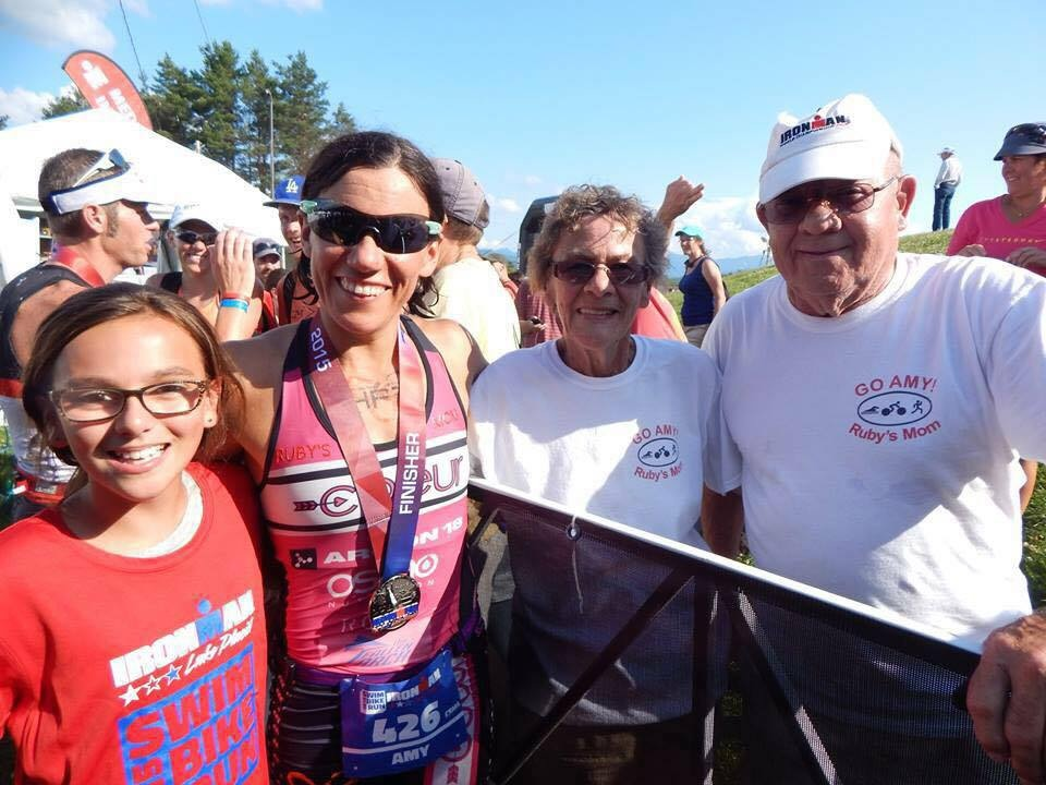 Amy Farrell flanked by her 11 year old daughter Ruby, left, and her parents, right, after becoming the 2015 Lake Placid Ironman Women's Overall Champion