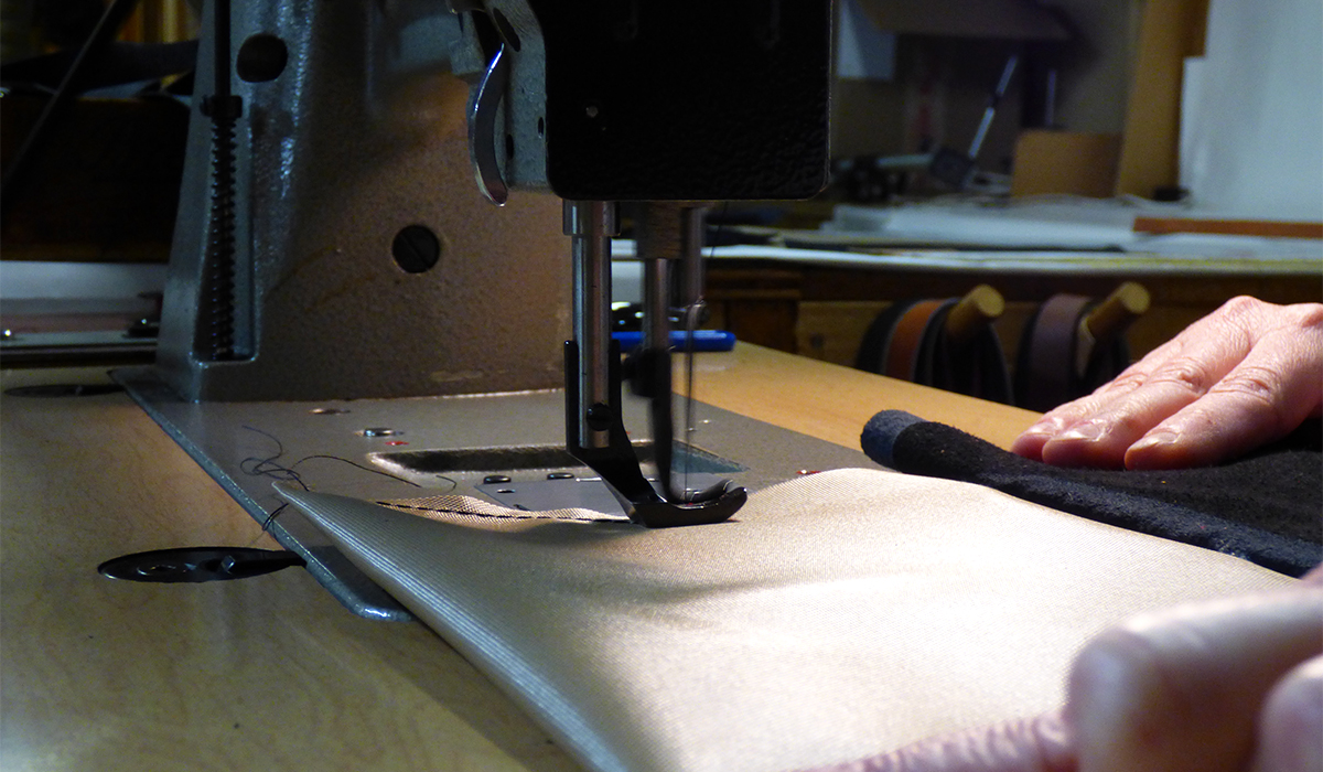 Artisans stitch the ripstop fabric lining for a leather handbag.