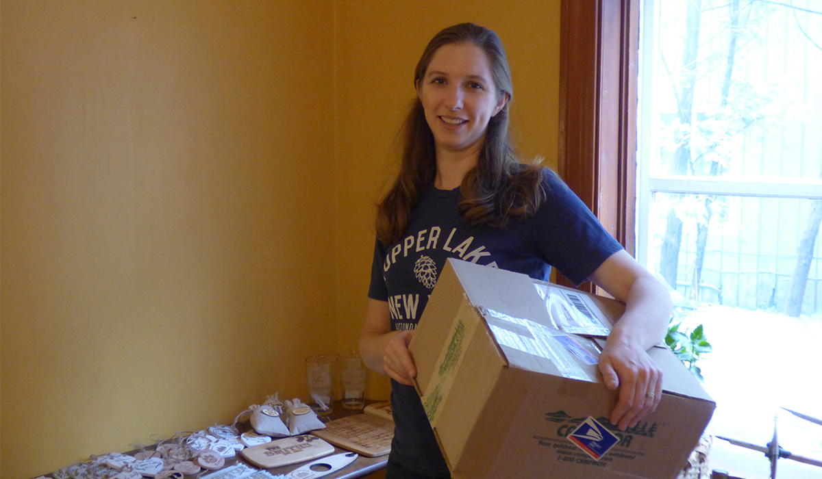 Store owner, Faith McClelland, carries one of the first of many boxes into what will soon be the Spruce & Hemlock Country Store