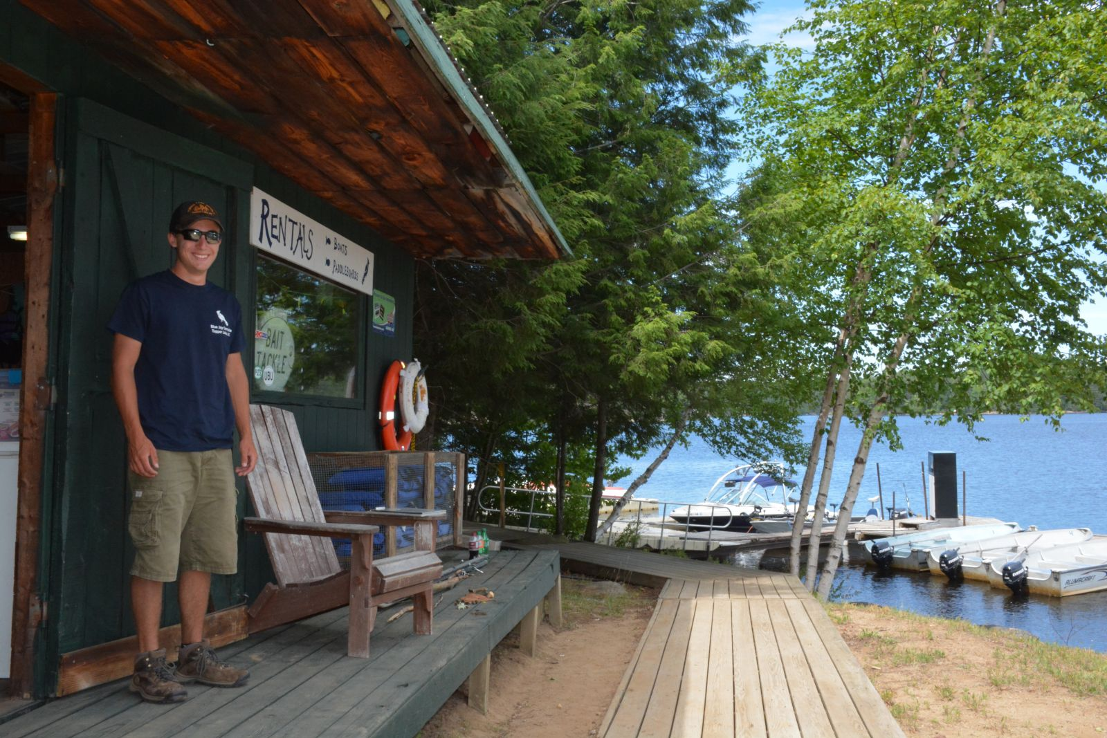 Mitch Harriman, a Blue Jay Campsite employee, stands in front of the marina's boathouse before heading down to the dock to help customers.