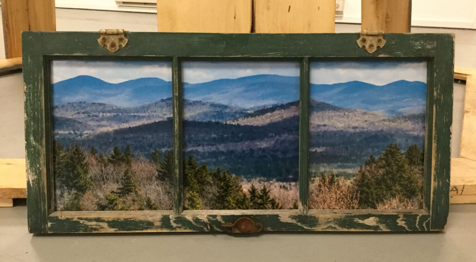 This repurposed window frame creates a perfect setting for the landscape view the artist has created.