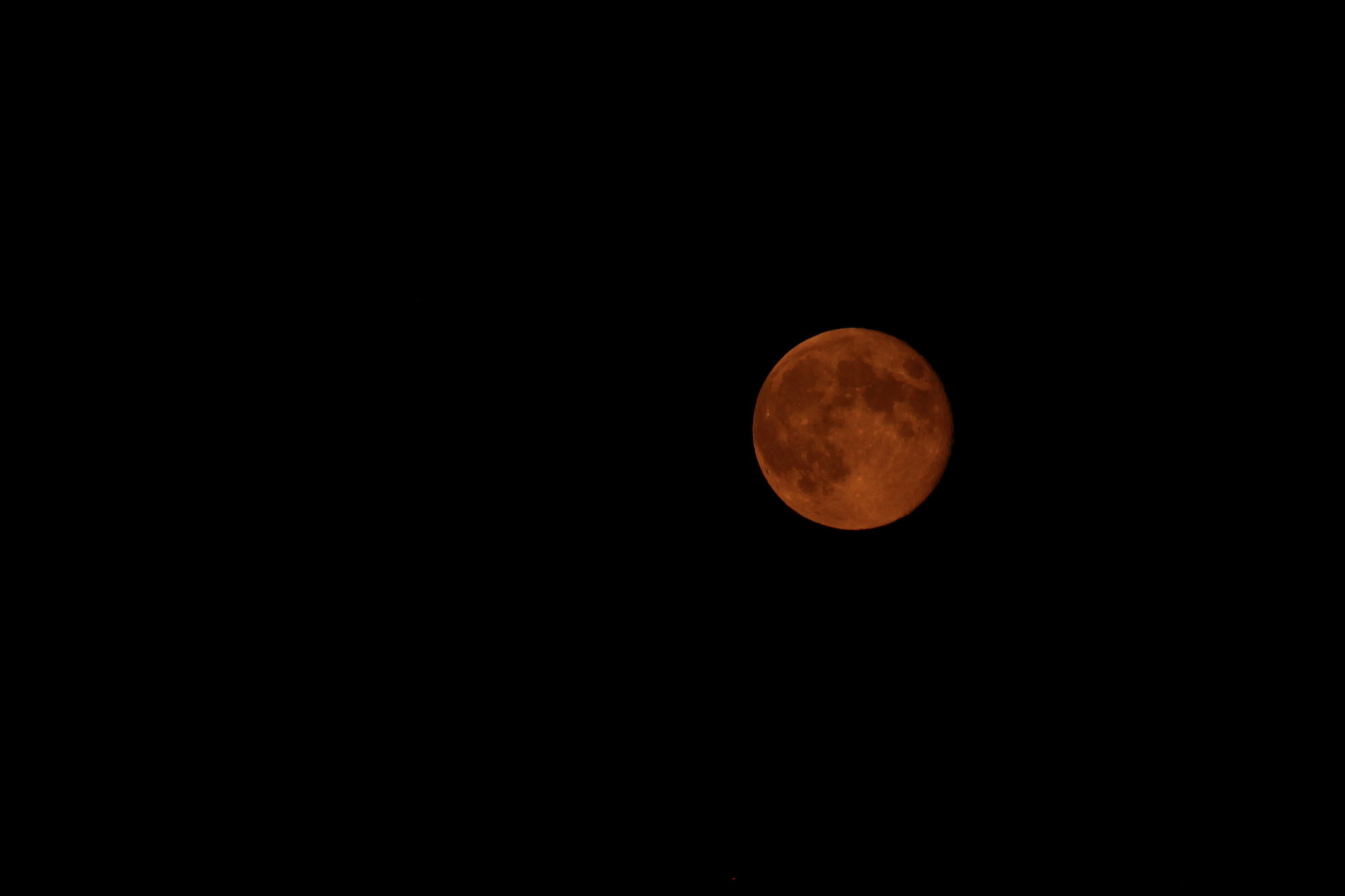 The moon appears reddish orange during a lunar eclipse.