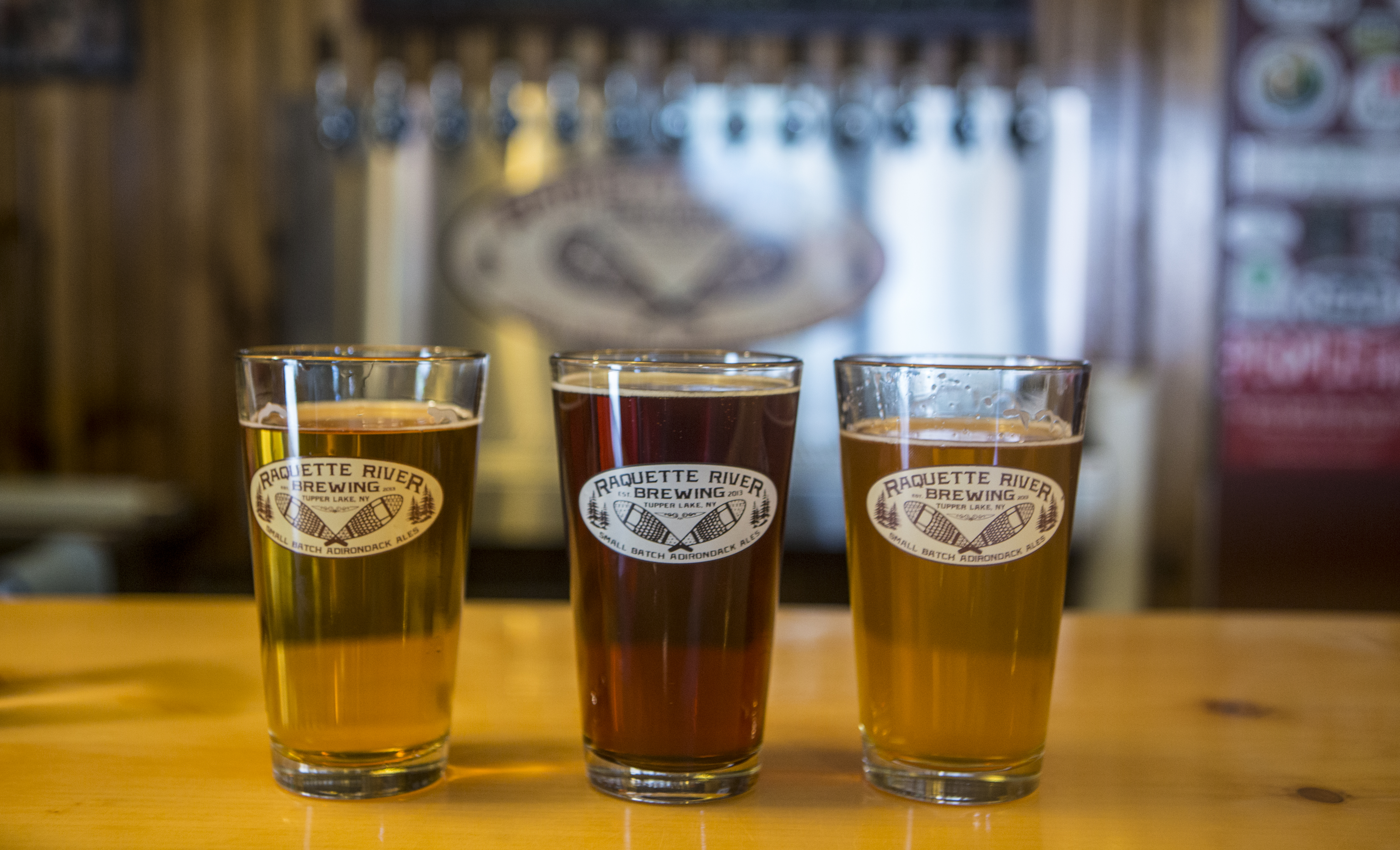Three beers hand-crafted at Raquette River Brewing aligned on the bar
