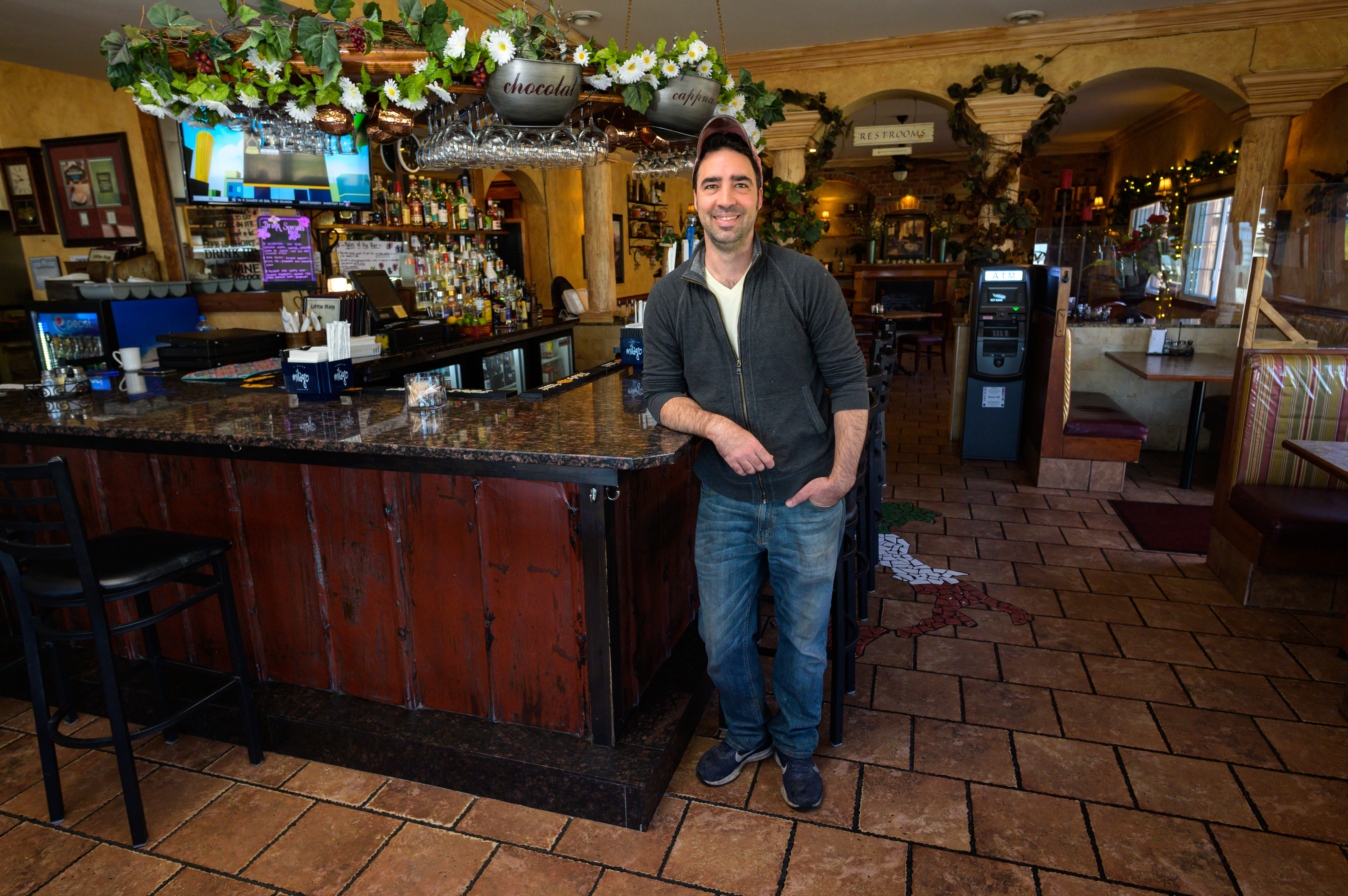 Portrait of Ted Demarais standing in front of his restaurant's bar
