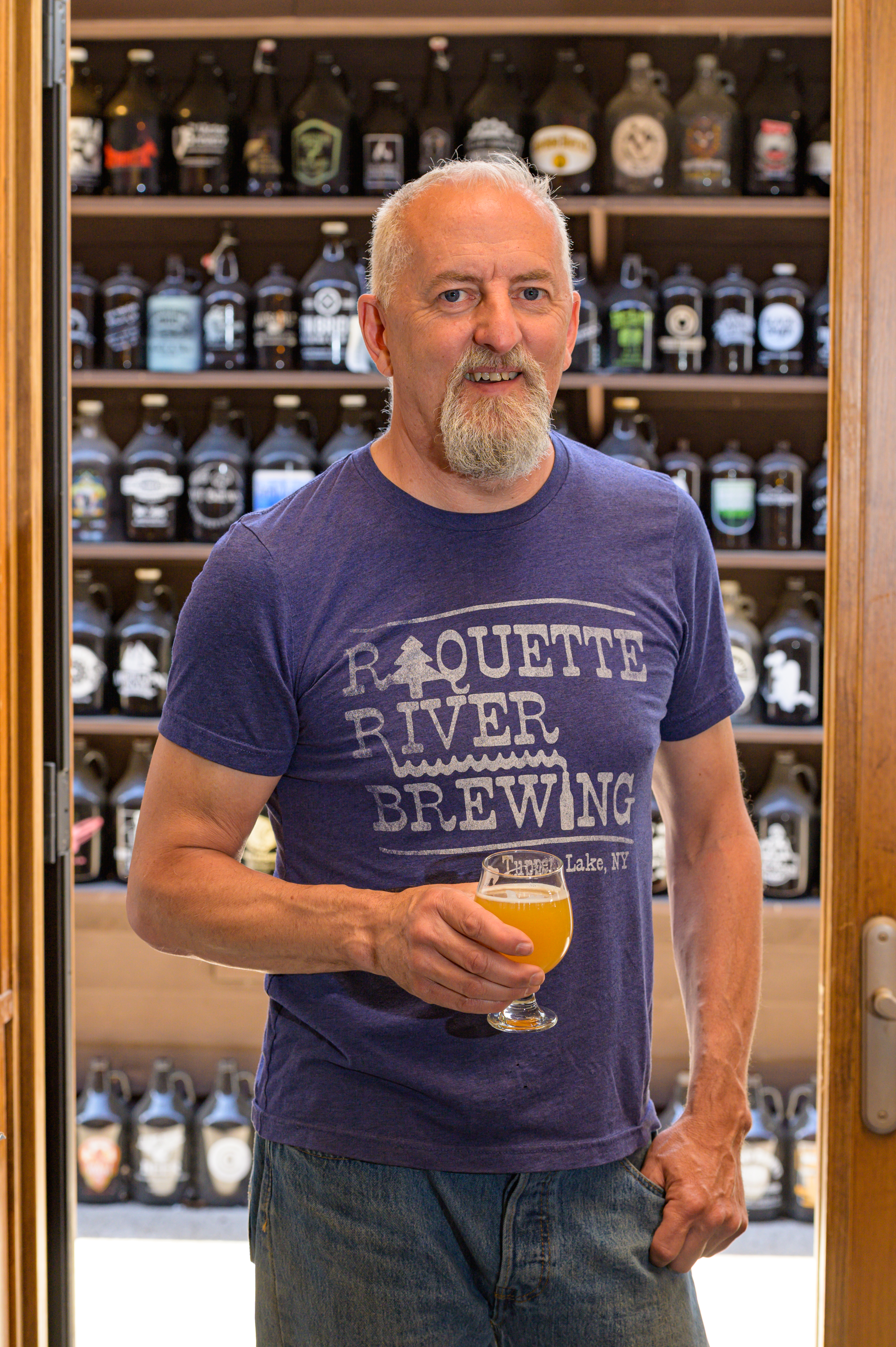 The co-owner of Raquette River Brewing, Mark Jessie, stands in front of growlers while holding a beer