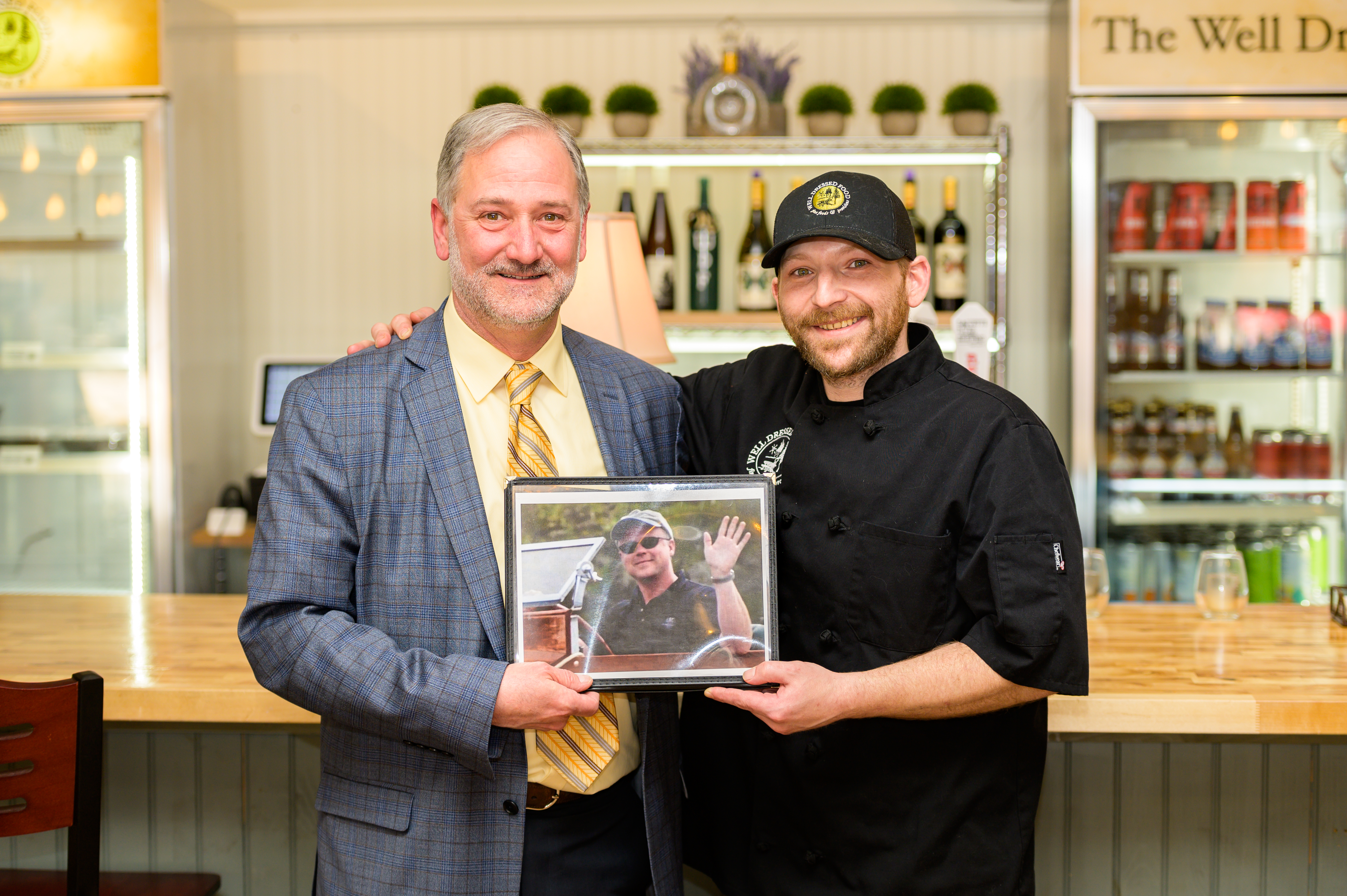 Owner Russell Cronin (left) and manager Mitch LaLonde (right) smile while holding a framed photo of David Tomberlin