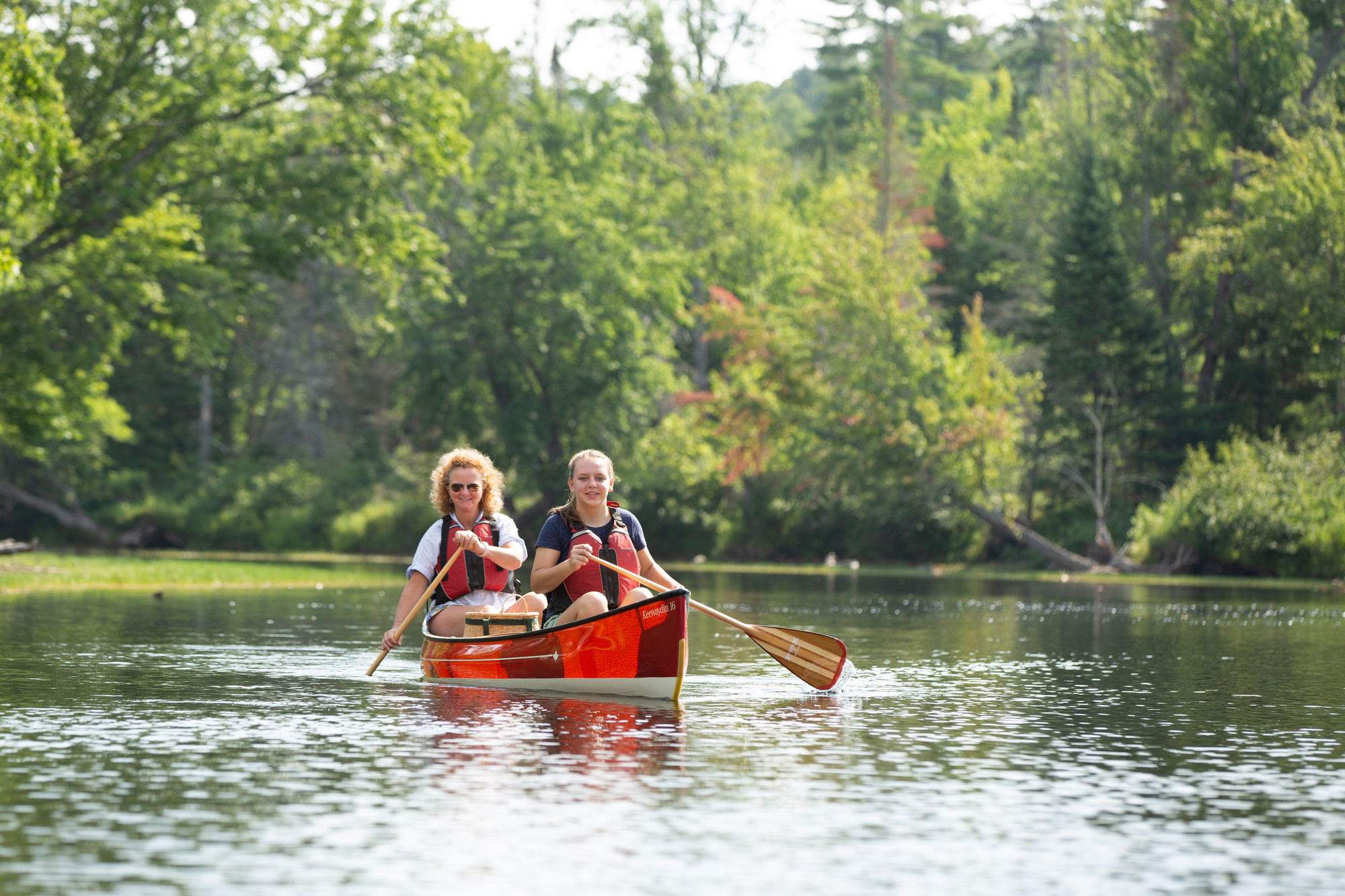 Two women paddle a red canoe along a river with trees in the background.