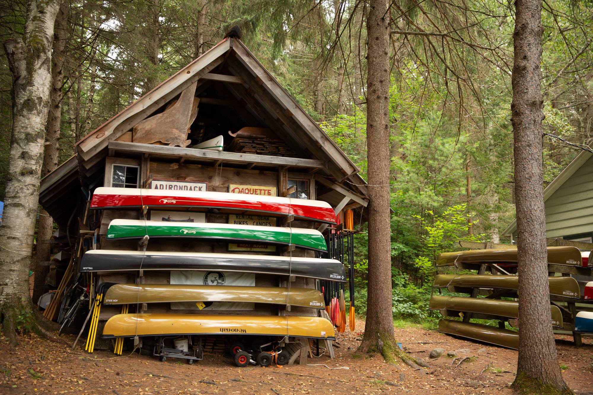 Canoe rentals stacked next to a wooden building.